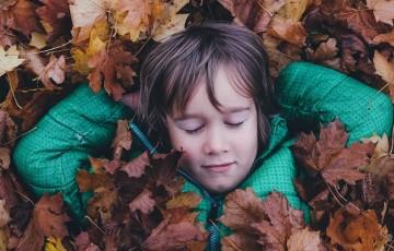 枯葉に埋もれる少年