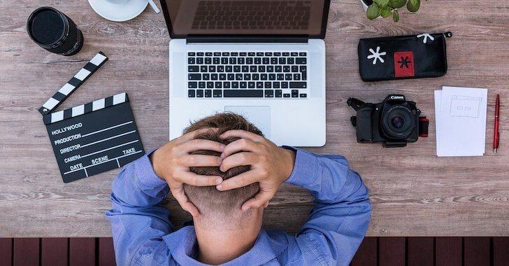 パソコンの前で頭を抱える男